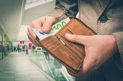 Wallet with euro money in male hands in shopping centre. Brown leather wallet with euro money in male hands in shopping centre - retro style stock photos