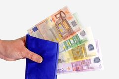 Wallet with Euro Notes. Blue purse with Euro notes in a hand - isolated on white background royalty free stock photography