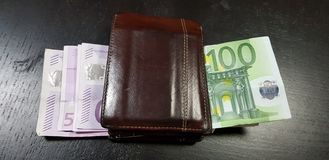 Wallet full with euro banknotes lay on black table royalty free stock photo