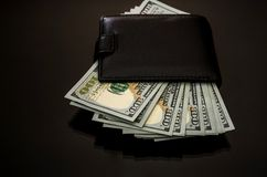 Wallet with hundred dollar bills on a black reflective background stock photography