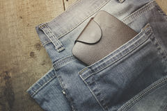 Wallet on jeans. Leather wallet wite jeans on the wooden table Royalty Free Stock Photography