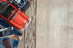Wallet in jeans pocket and toy car and retro cameras on wooden b Stock Photos