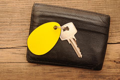 Wallet and key. With blank label on wood background Royalty Free Stock Photography