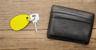 Wallet and key. With blank label on wood background Royalty Free Stock Photo