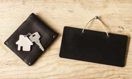 Wallet and key on wood background. Wallet with house and key on a wood background Stock Photography
