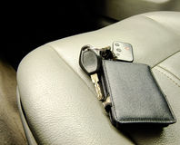 Wallet and Keys on the Front Seat. Black Wallet and Car Keys with Alarm Remote and Pendant on the Background of Front Leather Seat of A luxury Car Stock Image