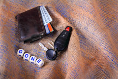 Wallet and Keys Gone. A mans worn wallet with new American hundred dollar bills showing and automobile keys laying on burlap gunny sack background with dice Royalty Free Stock Image