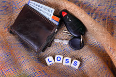 Wallet and Keys Loss. A mans worn wallet with new American hundred dollar bills showing and automobile keys laying on burlap gunny sack background with dice Stock Photo