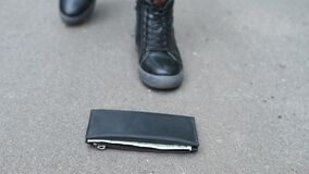Wallet lies on the pavement. girl in sneakers comes up to him and picks up