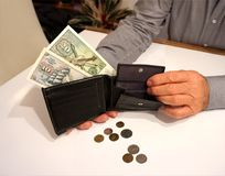 Wallet in man`s hand, with some banknote and coins. On the white table Stock Photos