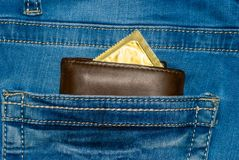 Wallet in a pocket of blue jeans with a gold condom Stock Photo