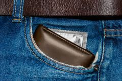 Wallet in a pocket of blue jeans with silver condom Stock Photos