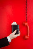Wallet and red phone. A view of the hand wearing a black suit, holding a wallet with money protruding next to a red telephone handset Royalty Free Stock Photos