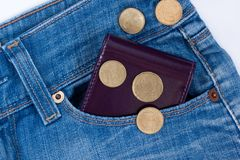 Wallet and small money are lying in side pocket of blue jeans stock images