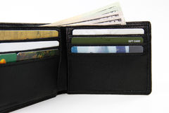 Wallet stuffed with cash and cards. Open wallet filled with gift cards, credit cards and money; white background; shallow focus and closeup view; landscape stock photos