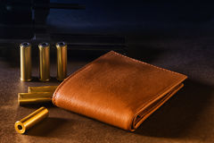 Wallet and weapons. And bullets. Showing the power of money and ammunition Stock Image