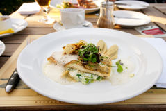 Walleye fillet with artichokes and molecular broth. On restaurant table Royalty Free Stock Images