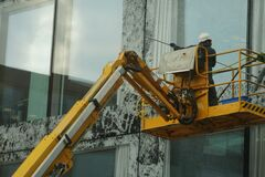 A man washing windows and facade of a building with a mop.