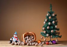 Wallnuts en una cesta de mimbre con un árbol de pino Foto de archivo
