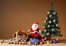 Wallnuts en una cesta de mimbre con un árbol y un santa de pino Foto de archivo