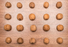 Wallnuts on wood ordered pattern background Stock Image