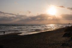 Walking at the beach at sunset. Stock Image