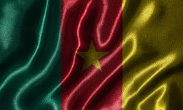 Wallpaper by Cameroon flag and waving flag by fabric. royalty free stock image