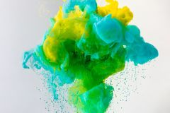 Wallpaper with flowing turquoise, yellow and green paint in water, isolated on grey stock images