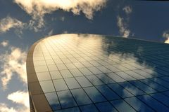 Wallpaper image with a skyscraper on a blue sky background. On a summer day with white clouds mirroring in the glass facade . Conceptual image with generic stock photography