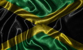 Wallpaper by Jamaica flag and waving flag by fabric. royalty free stock photo