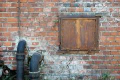 Wallpaper le mur avec les tuyaux de drainage et la fenêtre en métal Image stock