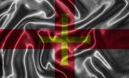 Wallpaper par le drapeau de Guernesey et le drapeau de ondulation par le tissu illustration libre de droits