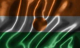 Wallpaper par le drapeau du Niger et le drapeau de ondulation par le tissu photographie stock