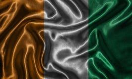 Wallpaper por la bandera de Costa de Marfil y la bandera que agita por la tela Foto de archivo