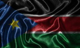 Wallpaper by South Sudan flag and waving flag by fabric. royalty free stock photography