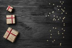 Wallpaper of winter holidays on black background. Gifts and gold stars. Space for text. Top view.  royalty free stock image