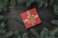 Wallpaper of winter holidays on black wooden background. Red gift in the middle of the frame of fir branches. Top view stock photo