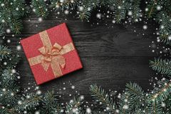 Wallpaper of winter holidays on black wooden background. Xmas greeting card with snow effect. Space for text stock photos