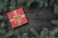 Wallpaper of winter holidays on black wooden background. Xmas greeting card. Space for text. A frame of fir branches and a red gift. Top view royalty free stock images