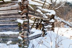 Walls of broken abandoned rural house in winter. Wooden walls of broken abandoned rural house at the edge of forest in sunny winter day in little village in Royalty Free Stock Images