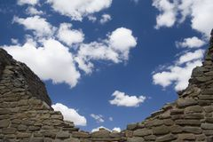 Walls at Chaco Canyon. A wall and puffy white clouds at the Aztec Ruins in  New Mexico Stock Photography