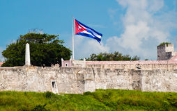 Walls of a fortress in Havana with a Cuban flag Royalty Free Stock Photography