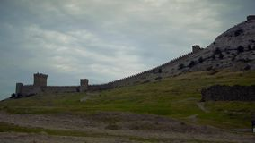 The walls of the Genoese Fortress. Slider. Light waves wash rocks on the beach stock video footage
