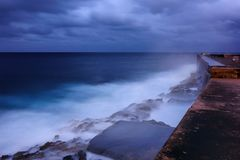 Walls of the Malecón in Havana, Cuba. Evening by the walls of the Malecón esplanade in Havana, Cuba and dramatic sea bounding water on the rocks Stock Photography