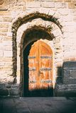 Walls of old fortress. Wooden door, entrance Royalty Free Stock Photos