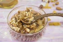Walnüsse, Haselnüsse und Honig in einem Glasteller Lizenzfreie Stockbilder
