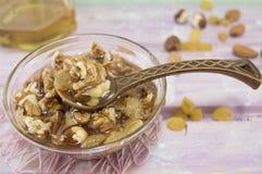 Walnüsse, Haselnüsse und Honig in einem Glasteller Lizenzfreies Stockfoto