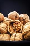 Walnüsse Nüsse von Walnüssen Nüsse in den Schwarzblechen vor dem hintergrund eines schwarzen hölzernen Hintergrundes rustic Lizenzfreie Stockfotos
