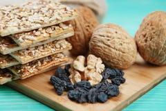Walnüsse, Rosinen und Kekse mit sortierten Samen über hölzerner Weinlesetabelle Stockfotos