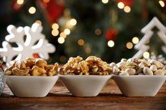 Walnusskern-Acajounüsse und pistachions in einer Schüssel auf dem Brett mit unscharfem christimas Hintergrund Stockfotos